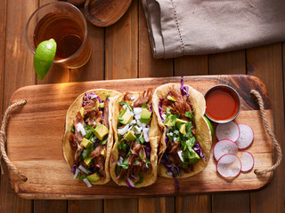 Sticker - mexican pork carnitas tacos with beer on wooden tray and radish garnish.