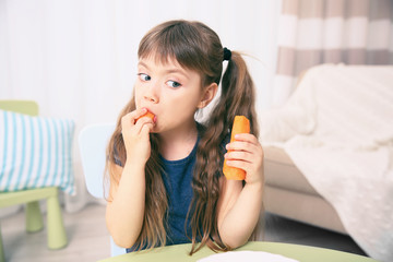 Little girl with carrot in the living room