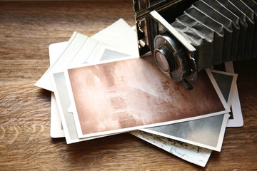 Vintage photos with camera on wooden background