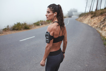 Fit young woman in sportswear standing on a country road