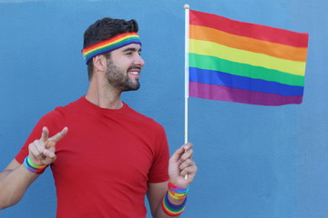 Fun LGBT community member standing holding and looking the beautiful rainbow flag