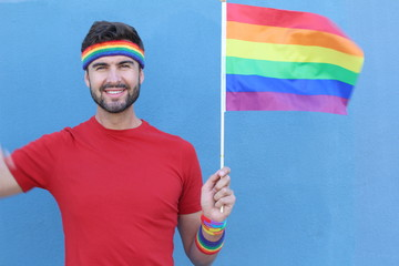 Gay male proudly holding the LGBT flag
