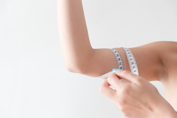 二の腕をを測る女性・白バック