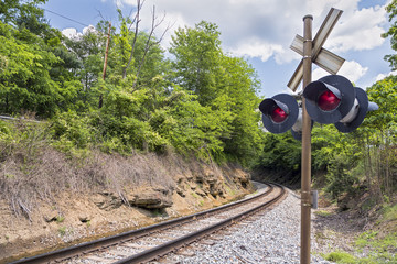 Curving Railroad Tracks and Crossing Signal in rural Wet virginia