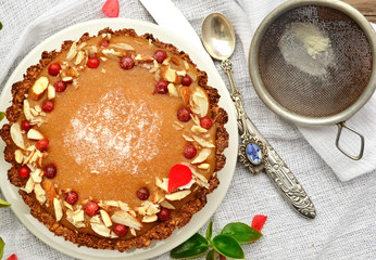 pie with plum jam, decorated with petals of almond on the white background
