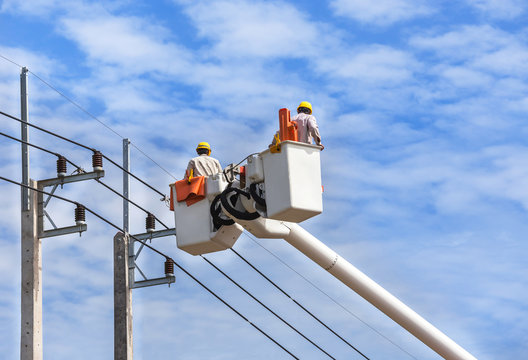 electricians repairing wire of the power line on hydraulic platform