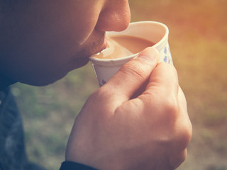 Man drinking a cup of masala chia tea with warm light