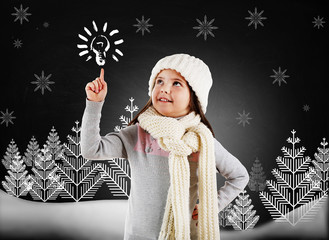 Little girl in a trendy knitted clothes looking up and drawn winter forest on blackboard background