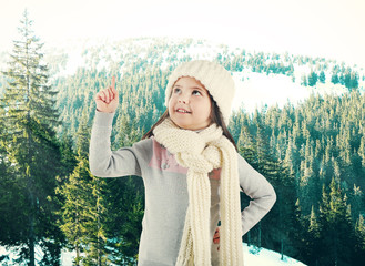 Little girl in a trendy knitted clothes looking up on winter forest background