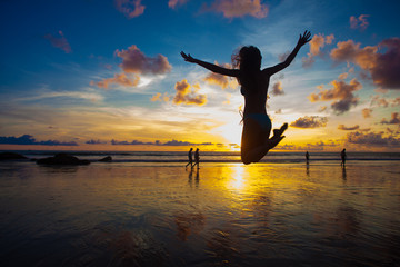 sunset silhouette of young fit woman jumping at beach