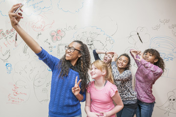 Girls taking selfie near whiteboard