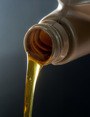 pouring engine oil from its plastic container.,dark background
