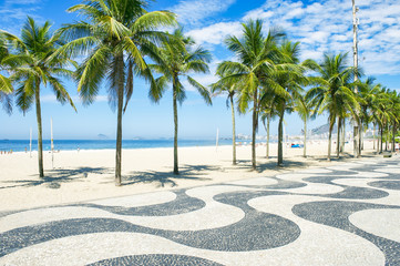 Iconic curving sidewalk tile pattern with palm trees at Copacabana Beach, Rio de Janeiro, Brazil