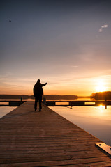 Man on a wooden jetty at lake, photographed in the evening, suns