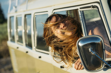 Teen girl sticking head out of van in motion