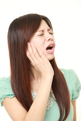 young Japanese woman wearing a green summer dress suffers from toothache