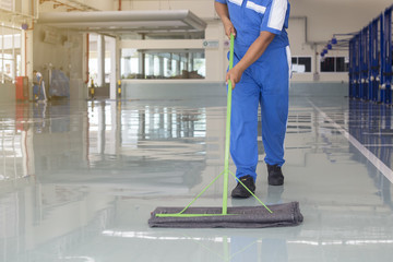 worker in blue, protective uniform cleaning new epoxy floor in e