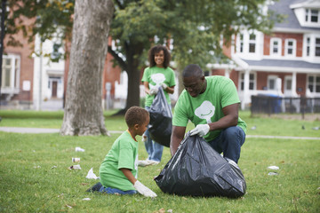 Family picking up garbage in park