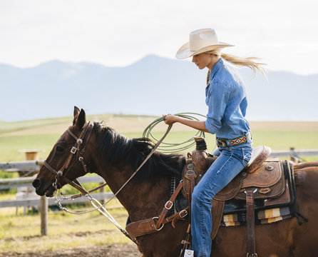 Caucasian cowgirl holding lasso on horseback