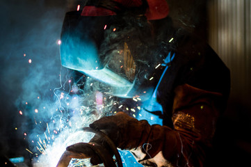 Worker welding in workshop
