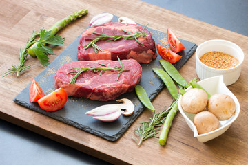 Raw beef steaks with ingredients on a black stone top view