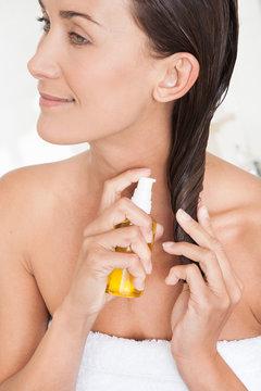 femme souriant mettant de l'huile sur ses cheveux
