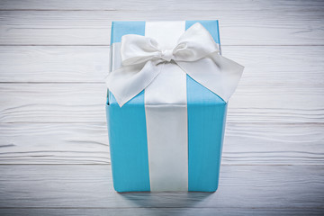 Gift box with white bow on wooden board celebrations concept