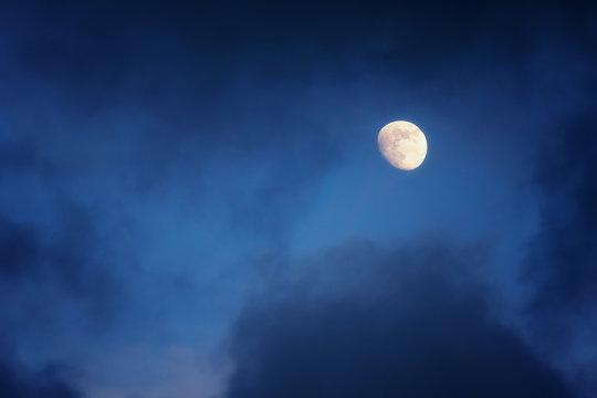 waxing gibbous moon on cloudy sky