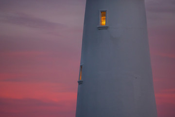 Cropped view of lighthouse with window illuminated