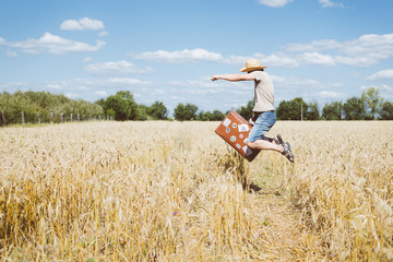 Man in hat jumping with old suitcase on wheat field summer sunny countryside.