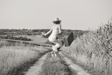 Black white photography of happy lady holding suitcase jumping high, countryside road background.