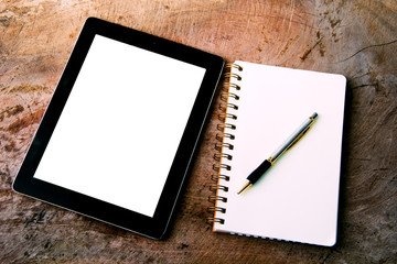 Blank notepad with tablet computer on office wooden table