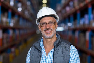 Portrait of happy worker is posing with hard hat
