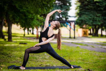 beautiful girl doing yoga on green grass in park at summer morning
