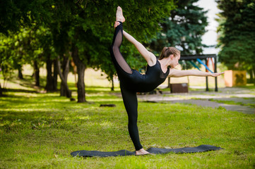 Balance exercise - young woman exercising in park