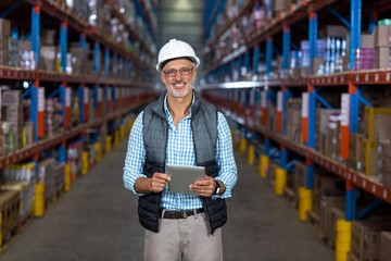 Portrait of happy worker is holding a tablet and posing