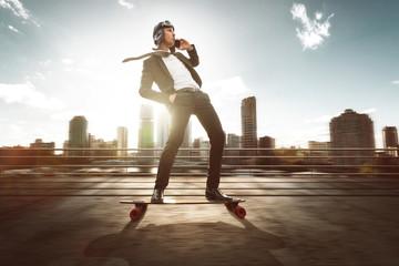 Geschäftsmann mit Smartphone auf Skateboard