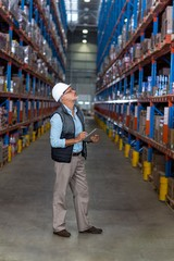 View of worker is looking shelves and holding a clipboard