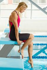 Female swimmer sitting  beside a pool