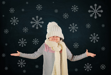 Confused little girl in a trendy knitted clothes and drawn snowflakes on blackboard background