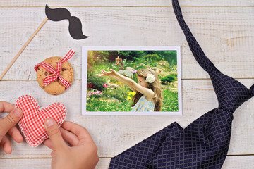 Child making present for father close up. Heart shape and and daughter's photo. Happy family concept