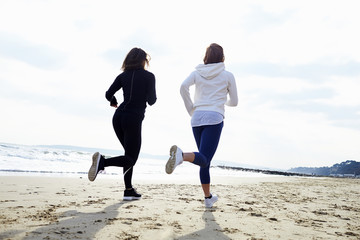 Two Female Friends Exercising By Running On Beach