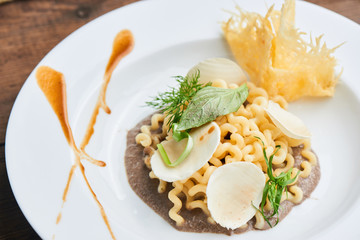 Pasta fusilli with mushroom sauce served on a white plate