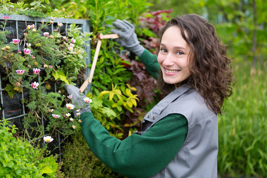 Young attractive landscaper woman working in a public park