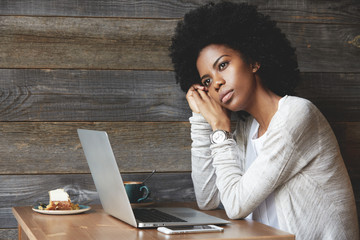 Attractive fashionable young African American female with clean healthy skin and Afro haircut, looking into the distance with thoughtful face dreaming of holidays while workin on laptop at a cafe
