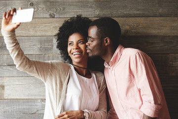 Love and affection concept. Beautiful young African woman with braces smiling and looking at the mobile phone screen, taking selfie while her boyfriend kissing her on the cheek with closed eyes