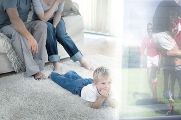 Boy lying on carpet is watching sport on television