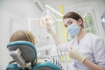 young woman doctor in a dental clinic. the dentist sits in the Cabinet beside the chair with the patient