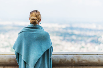 Back view of a woman with tied blond hair.