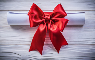 Paper roll with red bow on wooden board holidays concept